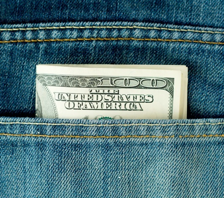 Blue jeans pocket with hundred dollars banknotes photo