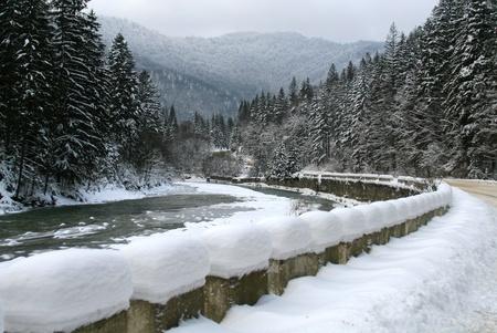 thorough: Snowy road thorough the mountains Stock Photo