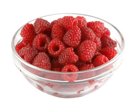 Ripe raspberries in a glass bowl isolated on white photo
