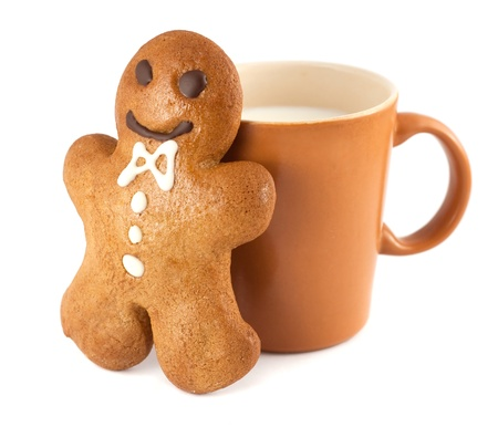 Gingerbread man with a cup of milk isolated on white photo