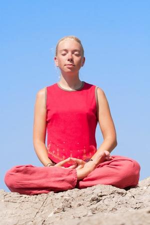 Beautiful girl making yoga exercise on a rock near the sea
