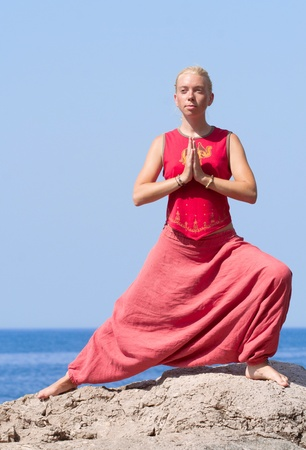 Beautiful girl doing yoga exercises on a rock by the sea