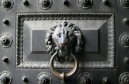 Old metal door with a lion head as a knocker