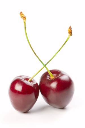 Two red cherries isolated on a white background photo
