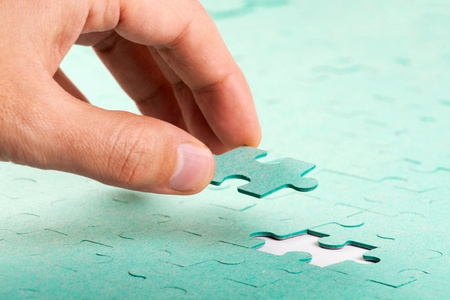 puzzle shape: Hand inserting missing piece of green jigsaw puzzle into the hole Stock Photo