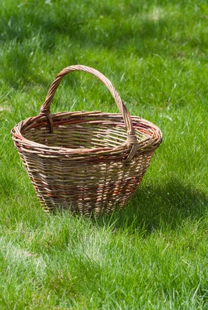 Old wicker basket on a green garden grass photo