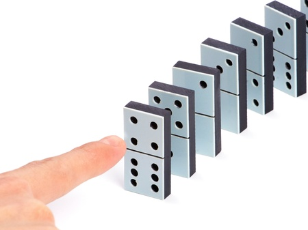 cause: Hand ready to push domino pieces to cause chain reaction