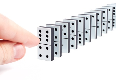 Hand ready to push domino pieces to cause chain reaction