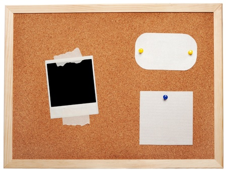 Blank instant photo and note papers on a cork board photo