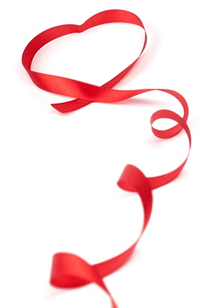Red ribbon curled in heart shape isolated on white background photo