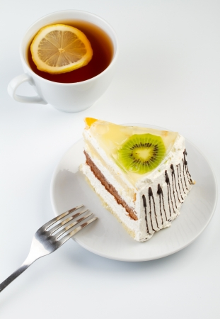 A cup of tea and a piece of tasty creamy cake with fruits Stock Photo - 16069061