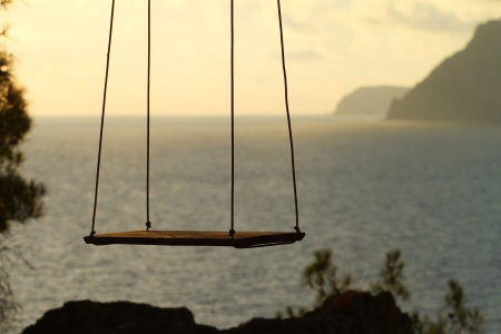 Wooden swing chair near the ocean photo