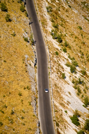Aerial view of a desert highway with a car driving on it photo