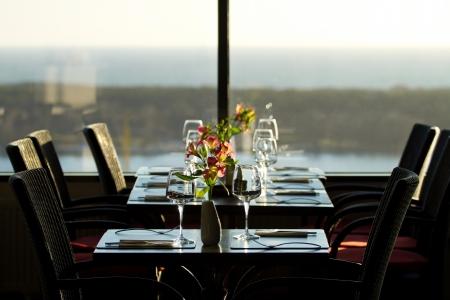 setting sun: Modern restaurant interior with scenic seaside view Stock Photo