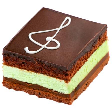 trozo de pastel: Pastel de chocolate con un signo clave de sol hecho con crema aislado en blanco