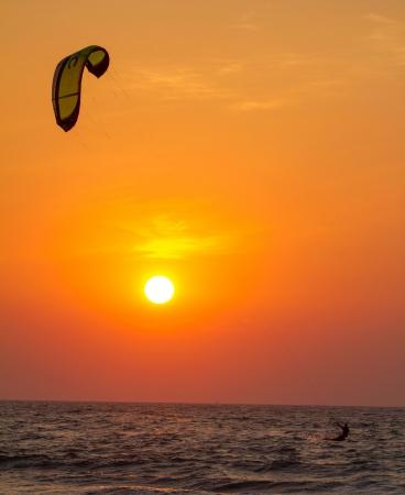 Silhouette of a kitesurfer st sunset photo