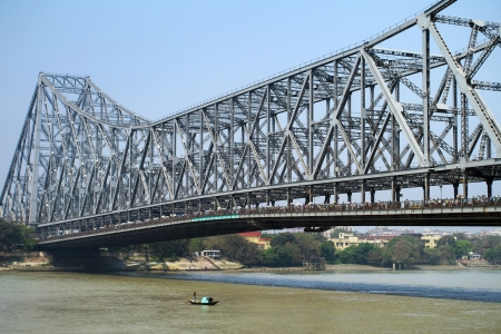 KOLKATA, INDIA - MARCH 13: Fisherman boat crosses the Hooghly River nearby the Howrah Bridge on March 13, 2013. Hooghly Bridge is a famous landmark in the city of Calcutta  Kolkata, India.