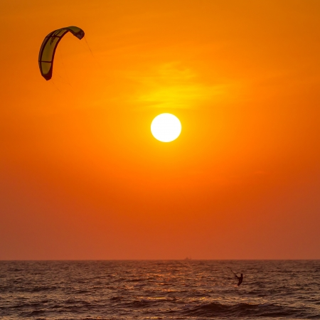 Silhouette of a kitesurfer st sunset photo