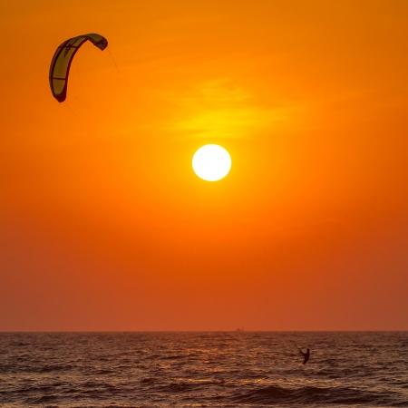 Silhouet van een kitesurfer st zonsondergang