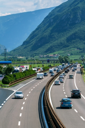 ITALY - JULY 7: Loaded cars driving on the highway during summer vacation on July 7, 2013 in Italian Alps.