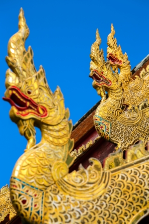 Golden dragon statues on the roof of buddhist temple in Thailand photo