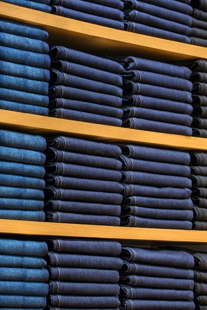 Neat stacks of folded clothing on the shop shelves photo