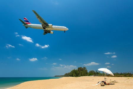 Airplane flying over the tropical island beach photo