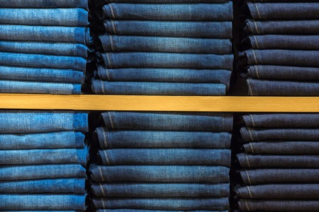 Neat stacks of folded jeans on the shop shelves photo