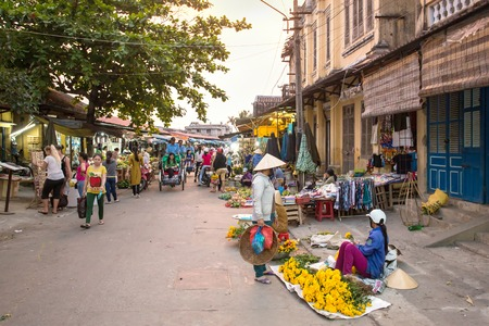 sidewalk sale: HOI AN, VIETNAM - MARCH 30: flower vendors and local farmers selling fresh products at the farmer market in Hoi An, Vietnam on March 30, 2014.