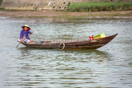 HOI AN, VIETNAM - MARCH 31: Woman driving the fishing boat in Hoi An, Vietnam on March 31, 2014.