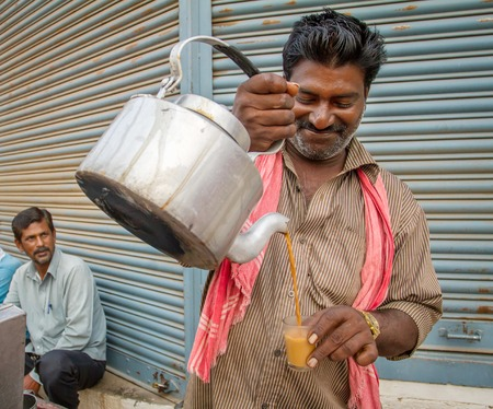 chai: MYSORE, INDIA - FEBRUARY 8, 2013 - Men pours cup hot milk tea Indian style or chai for customers from his shop along street