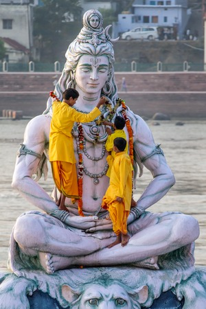 RISHIKESH, INDIA - NOVEMBER 13, 2012: Servants decorate large statue of Hindu Lord Shiva with flowers for the Ganga Aarti ceremony on November 13, 2012 in Rishikesh, India.