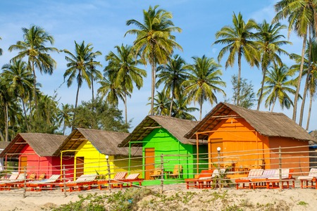 Goa: Colorful huts on the sandy beach with palm trees background in Goa, India Stock Photo