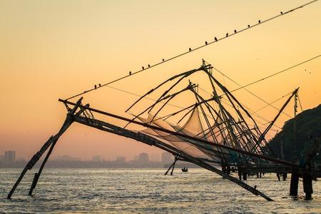 chinese fishing nets: Chinese fishing net at sunrise in Cochin (Fort Kochi), Kerala, India Stock Photo
