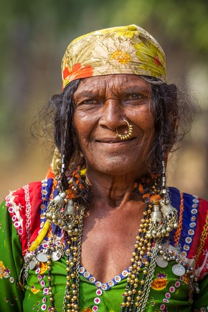 nomadic: HAMPI, KARNATAKA, INDIA - FEBRUARY 1, 2013: Unidentified old Banjari woman wearing traditional dress poses for the camera in Hampi, Karnataka, India on February 1, 2013. Banjara people are nomadic people from the Indian state of Rajasthan.