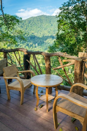Wooden table and chairs in the cafe with a wonderful mountain view. Northern Thailand. photo