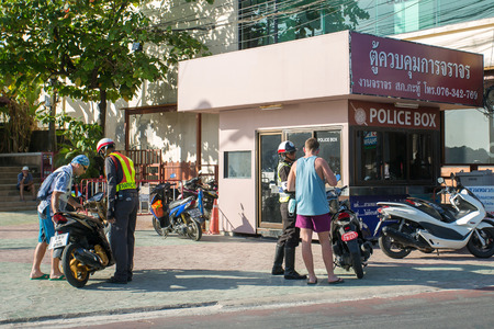 motorcycle officer: Phuket, Thailand - February 3, 2015: Road police check tourists on motorbike in Patong, Phuket, Thailand