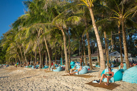 surin: Phuket, Thailand - January 24, 2015: People resting on the couches at the luxury Surin beach on Phuket, Thailand Editorial