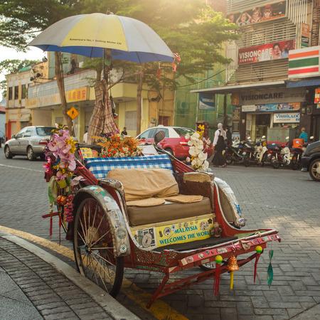 trishaw: Penang, Malaysia - February 25, 2015: An old traditional trishaw cab along a street in Penang, Malaysia.
