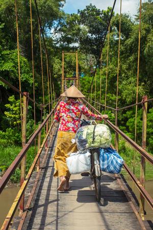 indonesian woman: Mujer indonesia en el sombrero tradicional de llevar bolsas en su bicicleta a trav�s del puente