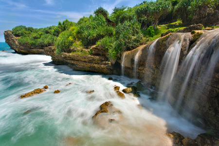 Beautiful Jogan waterfall falling to the ocean. Java, Indonesia