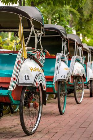 trishaw: Yogyakarta, Indonesia - April 2, 2015: Trishaws on the street of Yogyakarta, Indonesia Editorial
