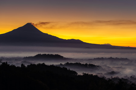 Colorful sunrise over Merapi volcano and Borobudur temple in misty jungle forest, Indoneisa 写真素材