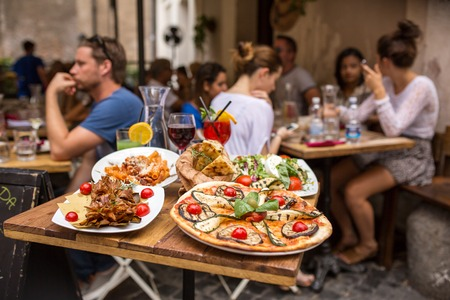 comida italiana: Roma, Italia - 11 de septiembre de 2015: La gente no identificada que comen comida tradicional italiana en el restaurante al aire libre en el barrio de Trastevere en Roma, Italia.