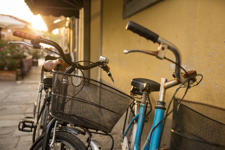 parked: Italian bicycles with baskets parked on empty sunny street Stock Photo
