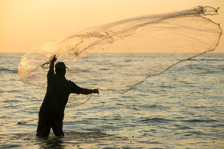 kochi: Silhouette of the unidentified Indian fisherman throwing net in sea on sunset in Fort Kochi, India.