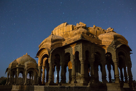 jainism: The royal cenotaphs of historic rulers, also known as Jaisalmer Chhatris, at Bada Bagh in Jaisalmer, Rajasthan, India. Night shot of ruins with stars Stock Photo