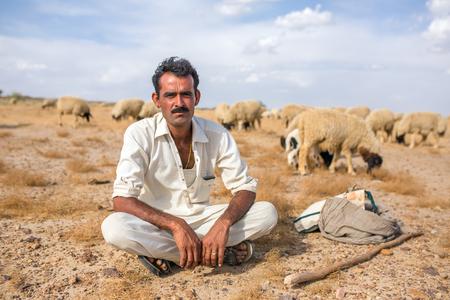 rajasthani: Jaisalmer, India - March 13, 2016: Portrait of unidentified rajasthani shepherd with his sheeps outside of Jaislamer, Rajasthan, India Editorial