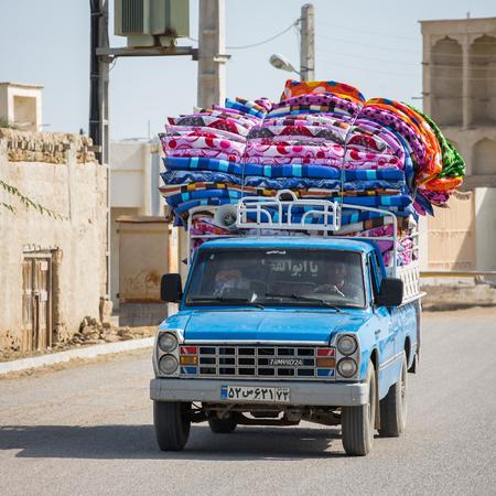 goods: Bandar-e Loft, Qeshm, Iran - December 20, 2015: Pickup car loaded with colorful mattresses rides around the streets calling customers in Bandar-e Loft village, Qeshm, Iran.