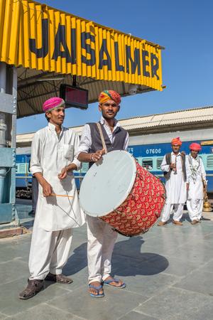 rajasthani: Jaisalmer, India - March 13, 2016: Traditional rajasthani musicians posing for photo under the big Jaisalmer sign on railway station.